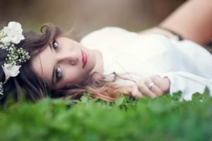 women, Model, Brunette, Long hair, Nature, White dress, Women outdoors, Flower in hair, Face, Blue eyes, Lying on back, Field, Depth of field, Looking at viewer