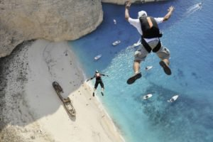 men, Sports, Jumping, Birds eye view, Sand, Helmet, Beach, Sea, Rock, Boat, Shipwreck, Sunlight, Greece, Parachutes