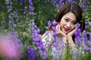 women, Model, Brunette, Long hair, Asian, Women outdoors, Nature, Field, Flowers, Grass, Smiling, Face, Looking at viewer, Depth of field, Red lipstick