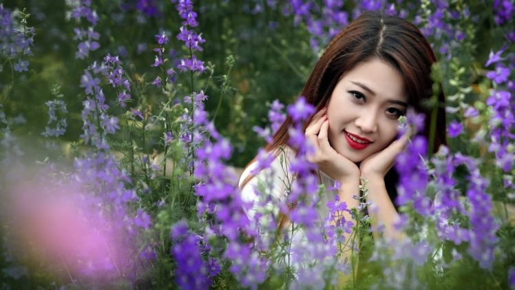 women, Model, Brunette, Long hair, Asian, Women outdoors, Nature, Field, Flowers, Grass, Smiling, Face, Looking at viewer, Depth of field, Red lipstick HD Wallpaper Desktop Background