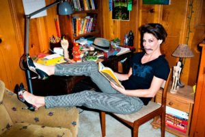 women, Model, Brunette, Sitting, High heels, Stiletto, Looking at viewer, Smiling, Evangeline Lilly, Short hair, Chair, Table, Interiors, T shirt, Pants, Reading, Wooden surface